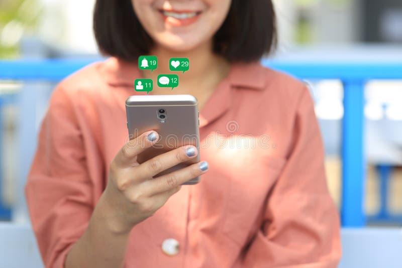 De holdingssmartphone van de vrouwenhand voor het controleren van sociale media met pictogram of hologram in koffie winkelt, comm stock fotografie
