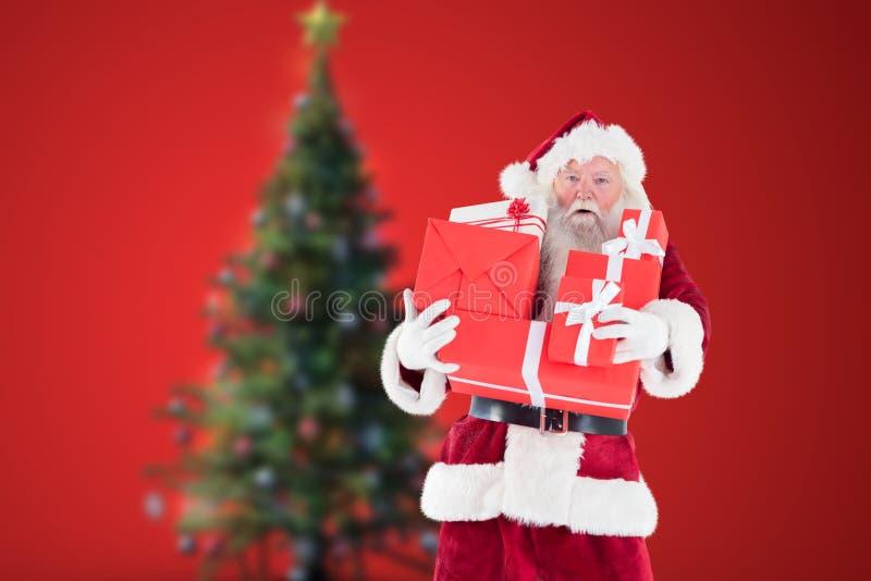 De holdingsstapel van de Kerstman Kerstmisgiften stock foto