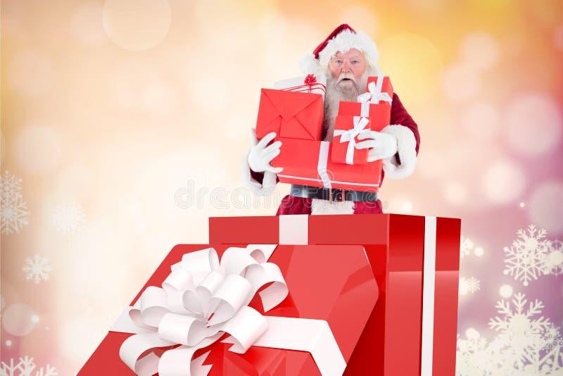 De holdingsstapel van de Kerstman Kerstmisgiften terwijl status binnen grote giftdoos royalty-vrije stock afbeelding