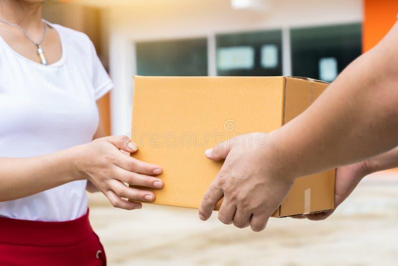 De de holdingsstapel van de leveringsmens van kartondozen in voorzijde die pakket leveren aan klant, sluit omhoog dichtbij en doo stock afbeeldingen