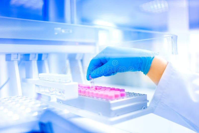 De holdingssteekproef van de wetenschapperhand in speciaal laboratorium, medisch milieu, het ziekenhuisdetails stock foto