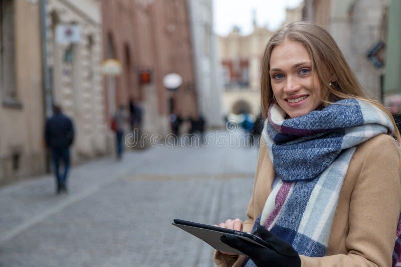 De holdingstablet van de blonde mooie vrouw op stadsstraat royalty-vrije stock afbeelding
