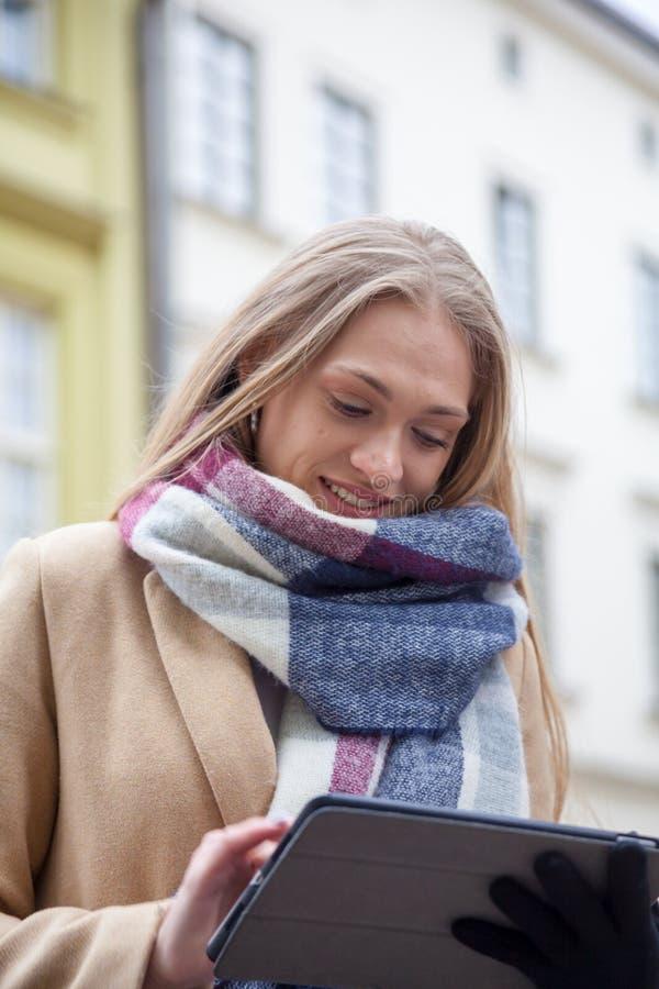 De holdingstablet van de blonde mooie vrouw op stadsstraat stock foto