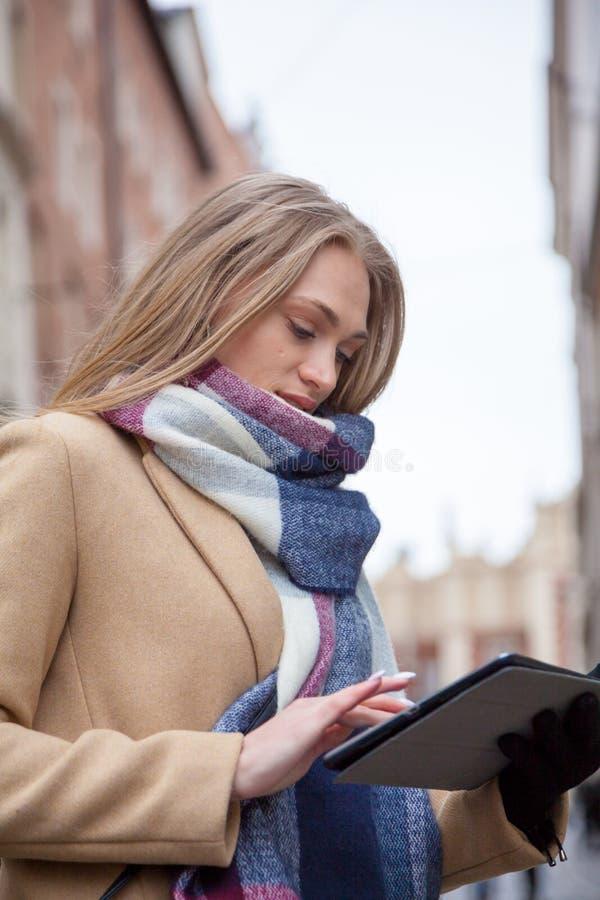 De holdingstablet van de blonde mooie vrouw op stadsstraat stock fotografie