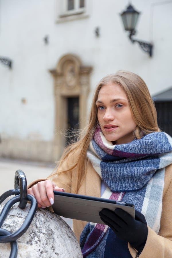 De holdingstablet van de blonde mooie vrouw op stadsstraat stock foto's