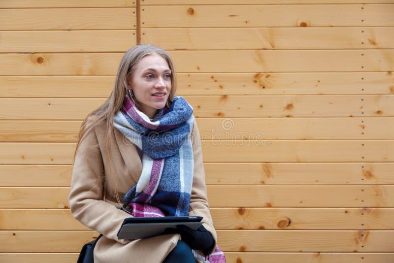 De holdingstablet van de blonde mooie vrouw openlucht stock fotografie