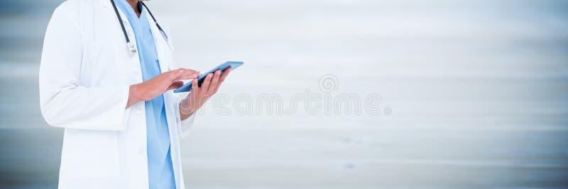 De holdingstablet van de artsen medio sectie tegen onscherp blauw houten paneel stock fotografie