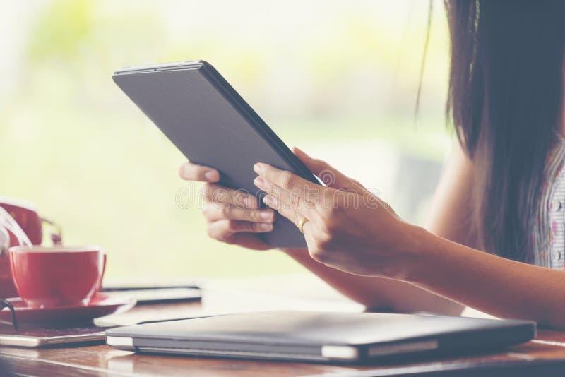 De holdingstablet van de vrouwenhand en het gebruiken van tablet in koffiewinkel stock afbeelding