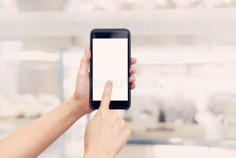 De holdingstelefoon van de handvrouw met het lege het scherm en onduidelijk beeld winkelen mal stock afbeelding