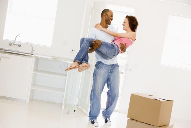 De holdingsvrouw van de echtgenoot in het nieuwe huis glimlachen stock foto's