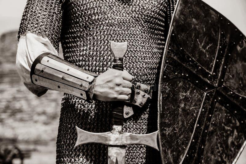 De holdingszwaard en schild van de riddermens stock afbeeldingen