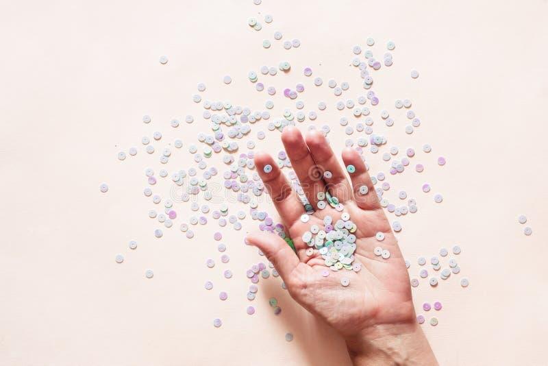 De holografische pastelkleur schittert confettien in vrouwelijke hand op roze achtergrond Creatieve conceptuele achtergrond royalty-vrije stock foto