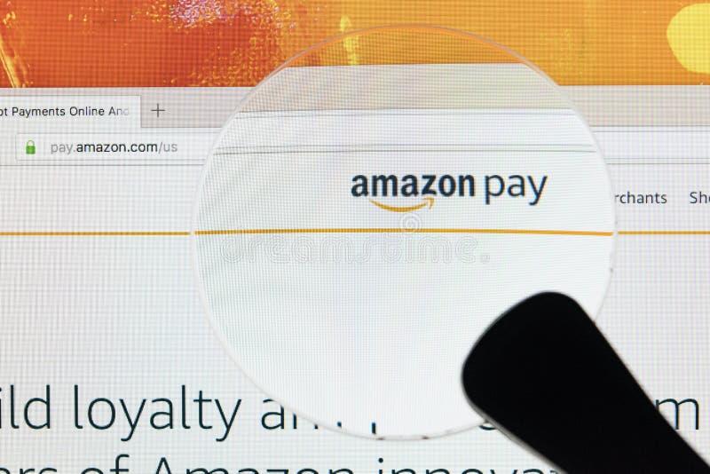 De homepage van online elektronische handelmarkt Amazonië betaalt op het scherm van de iMacmonitor onder vergrootglas De grootste stock fotografie