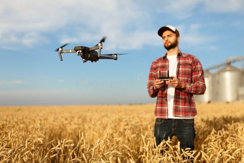 De hommel hangt voor landbouwer met ver controlemechanisme in handen dichtbij korrellift Quadcopter vliegt dichtbij proef royalty-vrije stock afbeelding