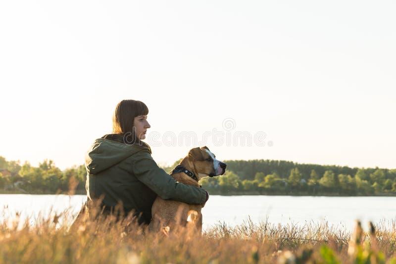 De hondeigenaar en haar huisdier zitten bij riverbank bij zonsondergang stock foto's