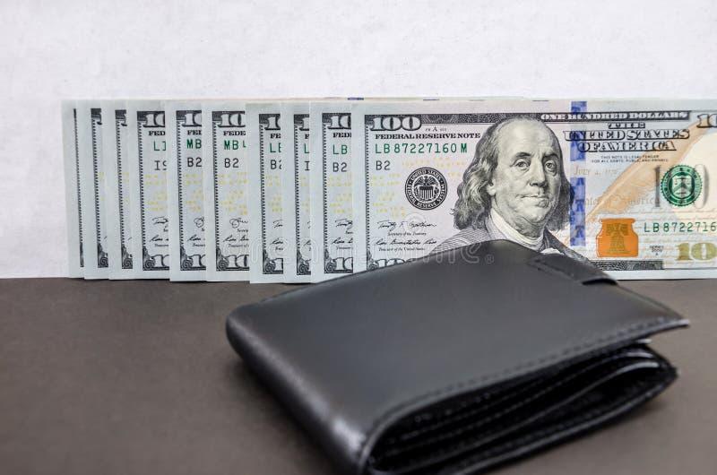 De honderd dollarsrekeningen vouwden op een rij en een zwarte portefeuille royalty-vrije stock foto's