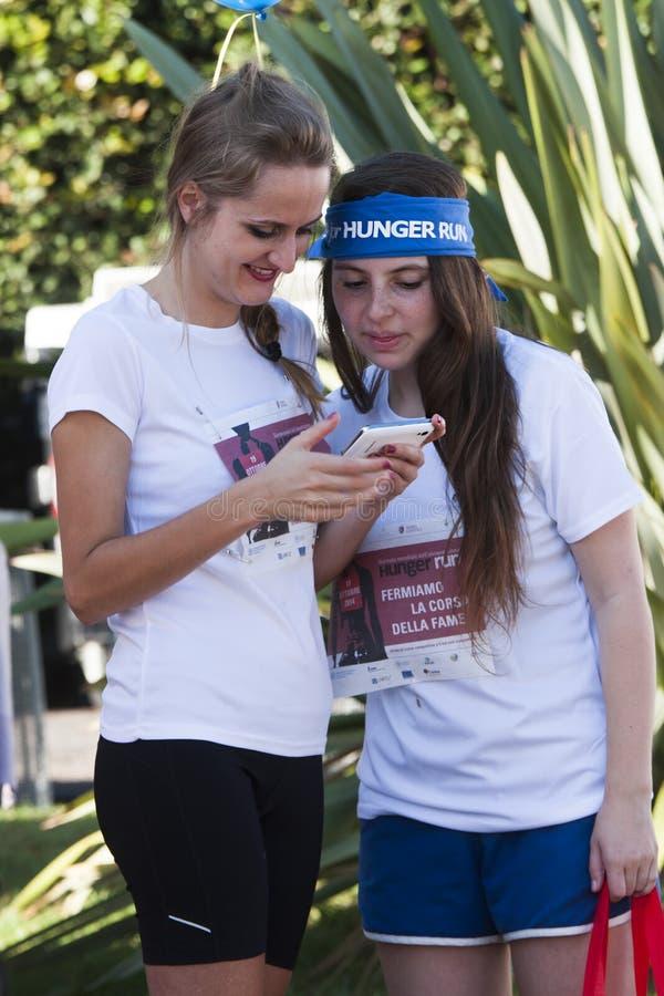 De honger loopt (Rome) - het WVP - Twee meisjes met mobiele telefoon stock foto