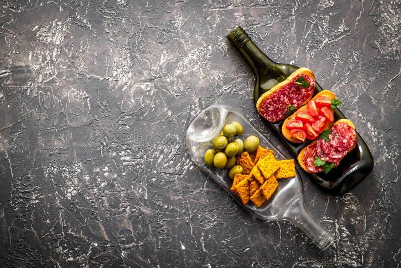 De honger van de wijn op flessen als dinnerware op de grijze lijst bekijkt exemplaarruimte royalty-vrije stock afbeeldingen