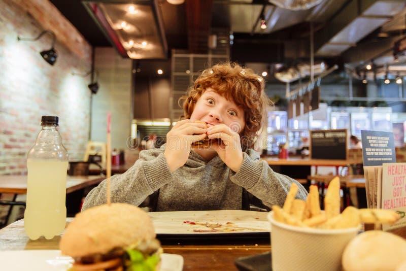 De hongerige jongen eet hamburger in restaurant stock afbeeldingen