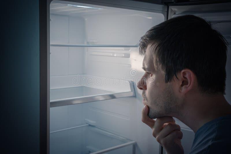 De hongerige mens zoekt voedsel in lege koelkast bij nacht te eten stock foto