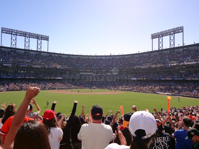 De honkbalventilators in gezet bleachers dient de lucht als toejuiching in tijdens spel stock foto