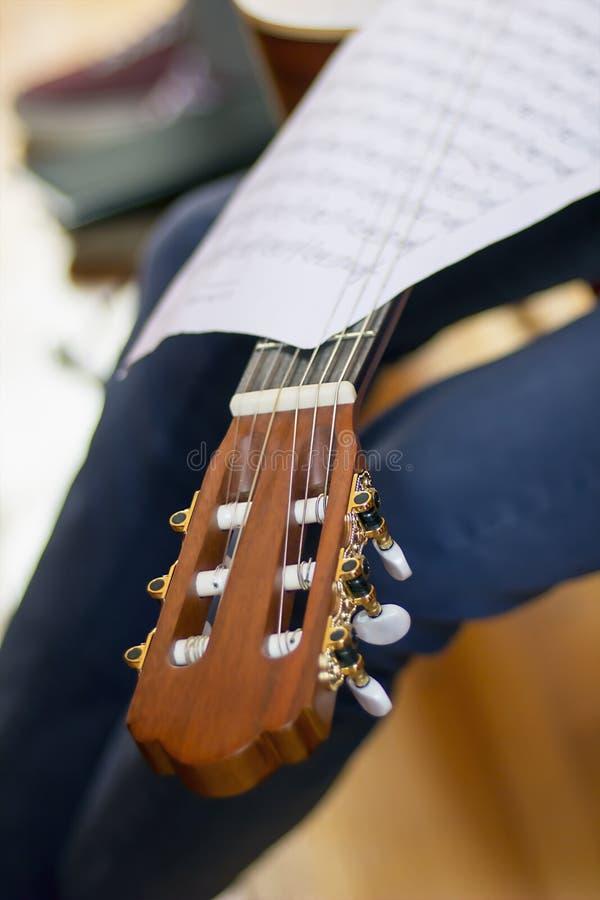 De hoofd en muzikale scores van de akoestische gitaar fretboard op een fretboa stock foto's