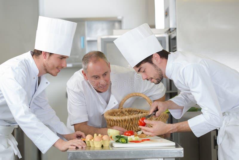 De hoofdcollega's van het chef-kokonderwijs hoe te om groenten te snijden stock foto