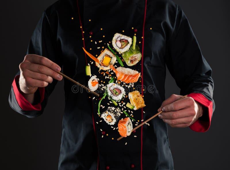 De hoofdeetstokjes van de chef-kokholding met vliegende sushi royalty-vrije stock foto's