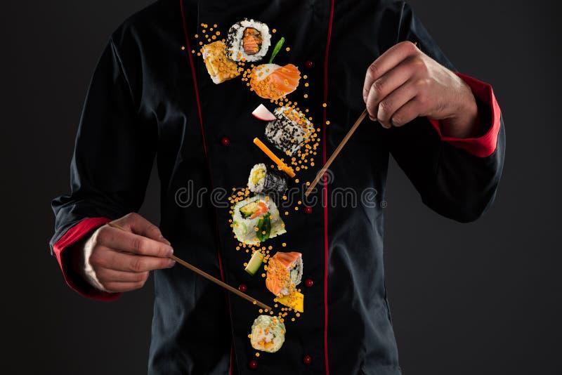De hoofdeetstokjes van de chef-kokholding met vliegende sushi stock fotografie