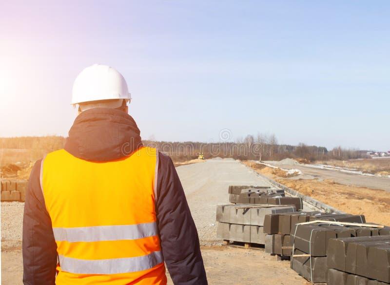 De hoofdmachinist in een witte helm en het signaal bekleden tegen de achtergrond van de bouw van een nieuwe weg en een rand, exem royalty-vrije stock foto