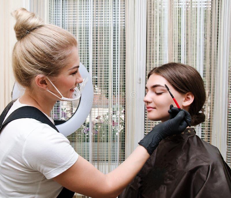 De hoofdmake-up verbetert geeft vorm en paintes wenkbrauwen in een schoonheidssalon stock foto
