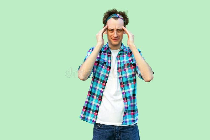 De hoofdpijn of verwart Portret van de droevige of zieke jonge mens in toevallig blauw geruit overhemd en hoofdband die en zijn h royalty-vrije stock fotografie