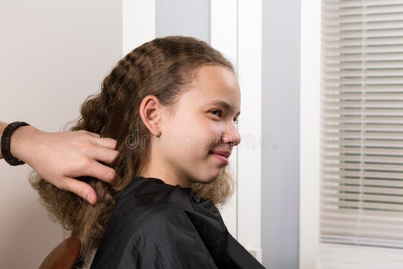De hoofdstilist behandelt het meisjes` s haar, voor het verdere leggen van krullende krullen royalty-vrije stock afbeelding