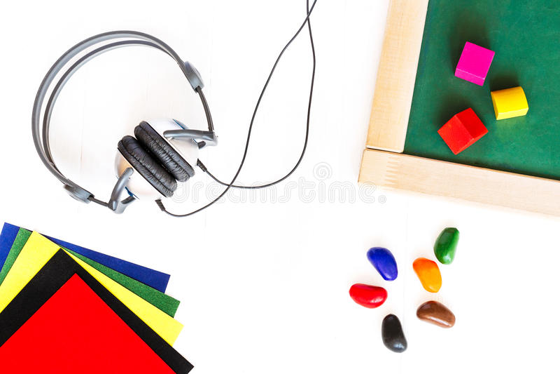 De hoofdtelefoons, schoolraad, kleurden blokken, waskleurpotloden, gekleurd document die op een witte houten achtergrond liggen H royalty-vrije stock afbeeldingen