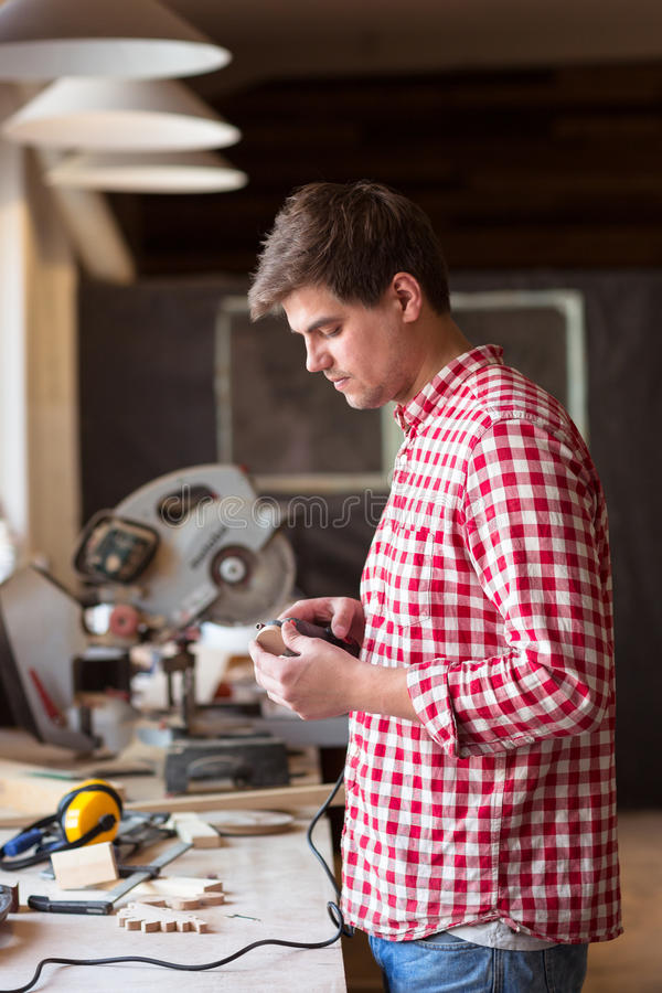 De hoofdtimmerman maalt Roterend hulpmiddelen houten stuk van houten stuk speelgoed Di royalty-vrije stock afbeeldingen
