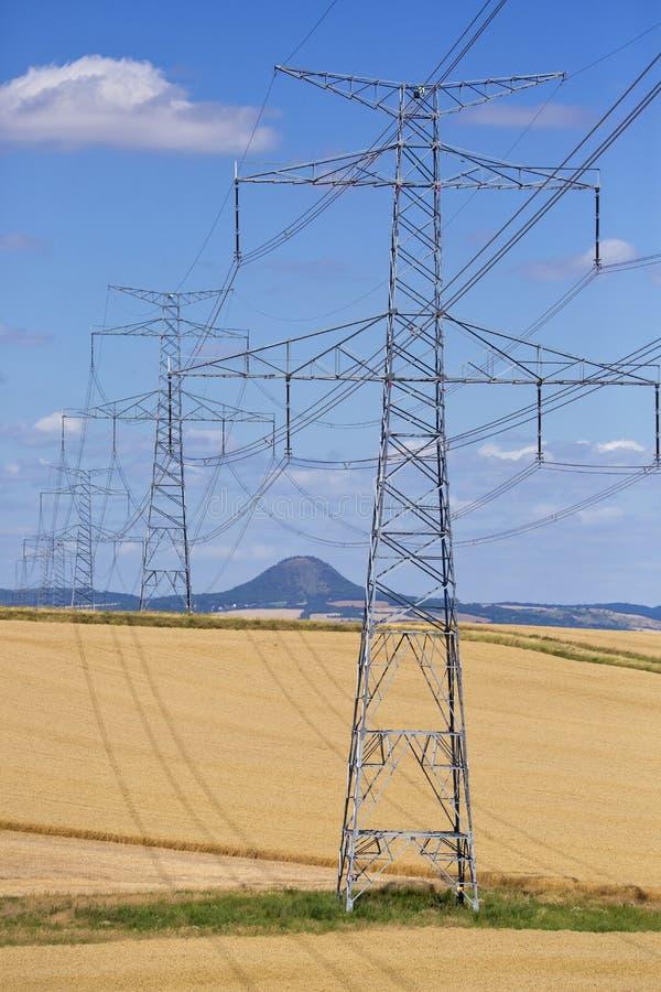 De hoogspanningslijnen en de machtspylonen in een groen landbouwlandschap op een zonnige dag met cirrus betrekken in de blauwe he stock foto