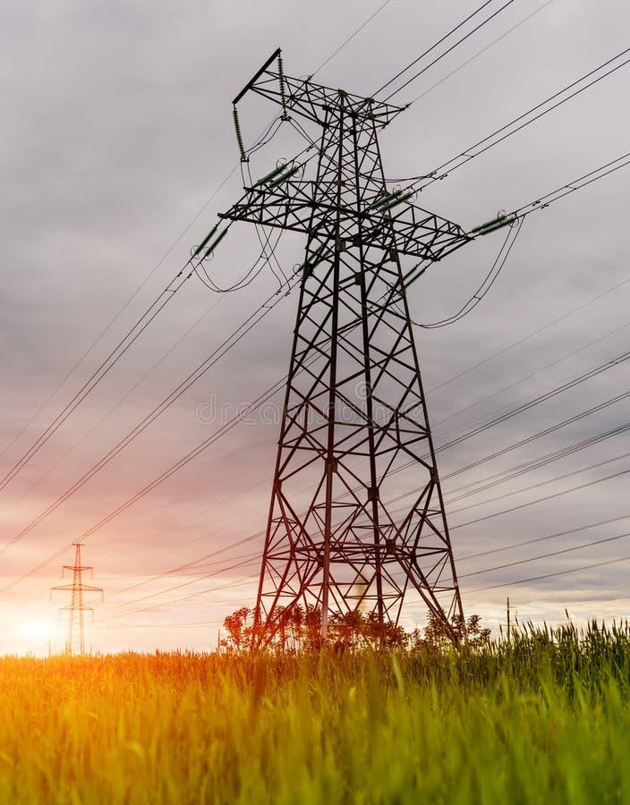 De hoogspanningslijnen en de machtspylonen in een vlak en groen landbouwlandschap op een zonnige dag met cirrus betrekken stock afbeelding