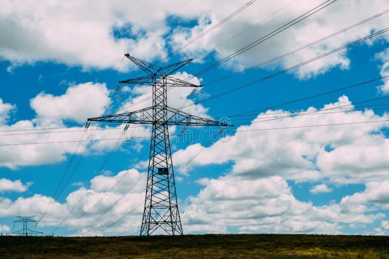 De hoogspanningslijnen en de machtspylonen in een vlak en groen landbouwlandschap op een zonnige dag met cirrus betrekken in royalty-vrije stock foto