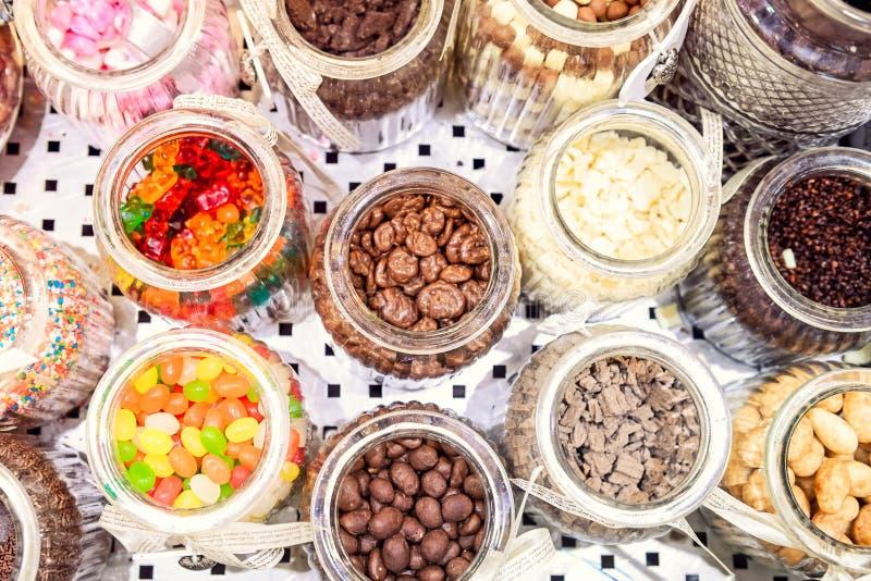 De hoogste containers van het meningsglas met diverse additieven aan roomijs Keus van vuller - suikergoed, noten, geleisnoepjes,  royalty-vrije stock afbeelding
