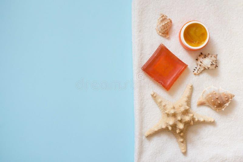 De hoogste cosmetischee productenroom en de oranje zeep met shells en het overzees spelen op witte handdoek op blauwe achtergrond stock fotografie