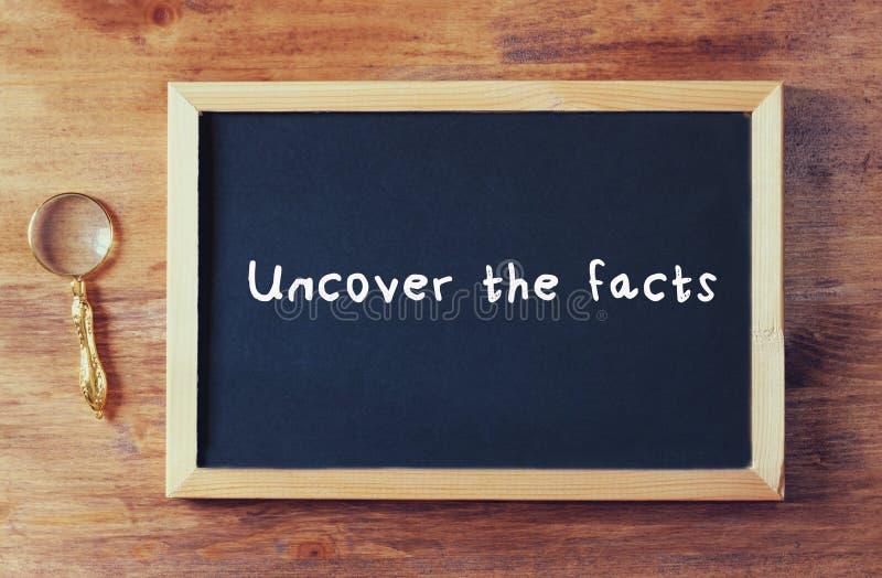 De hoogste die mening van bord met de uitdrukking brengt de feiten aan het licht op het naast oud vergrootglas over houten lijst  royalty-vrije stock foto's