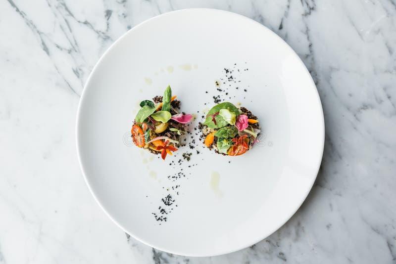 De hoogste die mening van Quinoa canapes bovenste laagje met pan schroeide asperge, tomaten en babygroenten en olijfolie op witte stock afbeelding
