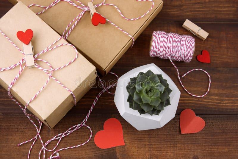 De hoogste dozen van de meningsgift met doekpinnen met rode harten en succulent in concrete pot stock afbeeldingen