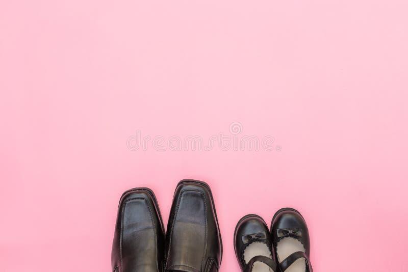 De hoogste laarzen van de meningspapa met het kind van het dochtermeisje op roze achtergrond stock afbeelding
