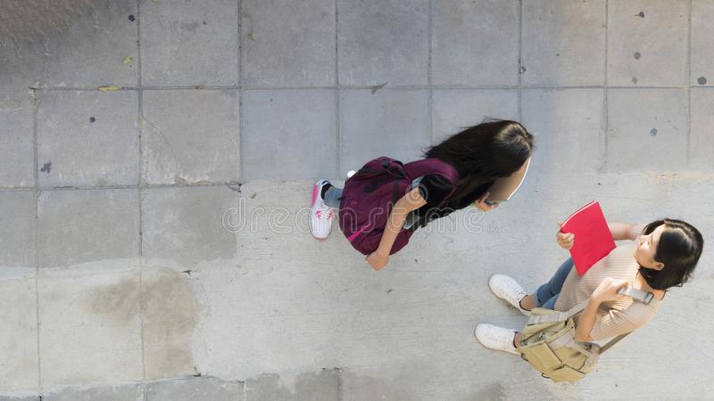 De hoogste lucht de meisjesbespreking van de meningstiener en komt bij voetgangmanier samen stock fotografie