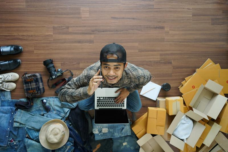 De hoogste mening die van de Aziatische mens slimme telefoon werkende laptop houden verwerkt gegevens royalty-vrije stock afbeelding