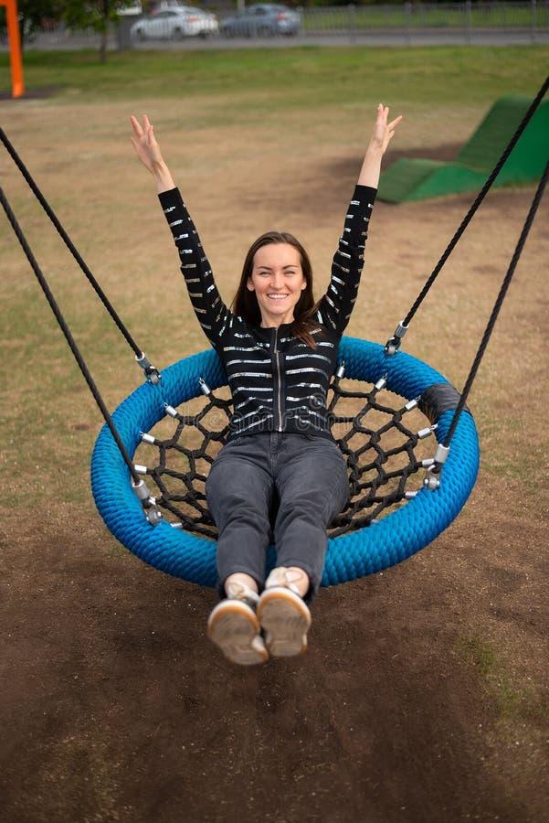 De hoogste mening die van jonge vrouw bij het hangen van schommeling slingeren overhandigt op weg het glimlachen, concept vrijhei stock foto