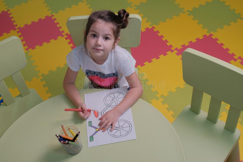 De hoogste mening een leuk meisje trekt een beeld van een Fiets met kleurpotloden Grappig kind die pret in de Studio van de kinde royalty-vrije stock afbeelding