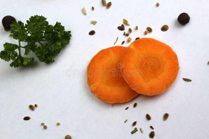 De hoogste mening, een plak van wortelen, peterselie ligt op een witte oppervlakte stock fotografie