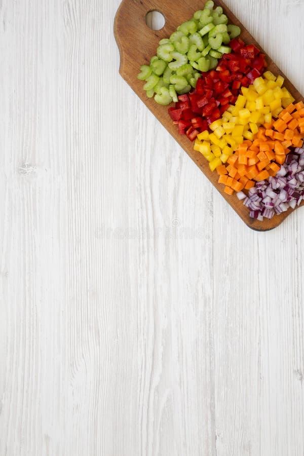 De hoogste mening, gehakte verse groentenwortel, selderie, rode ui, kleurde peper die op scherpe raad op een houten wit wordt ges stock afbeeldingen